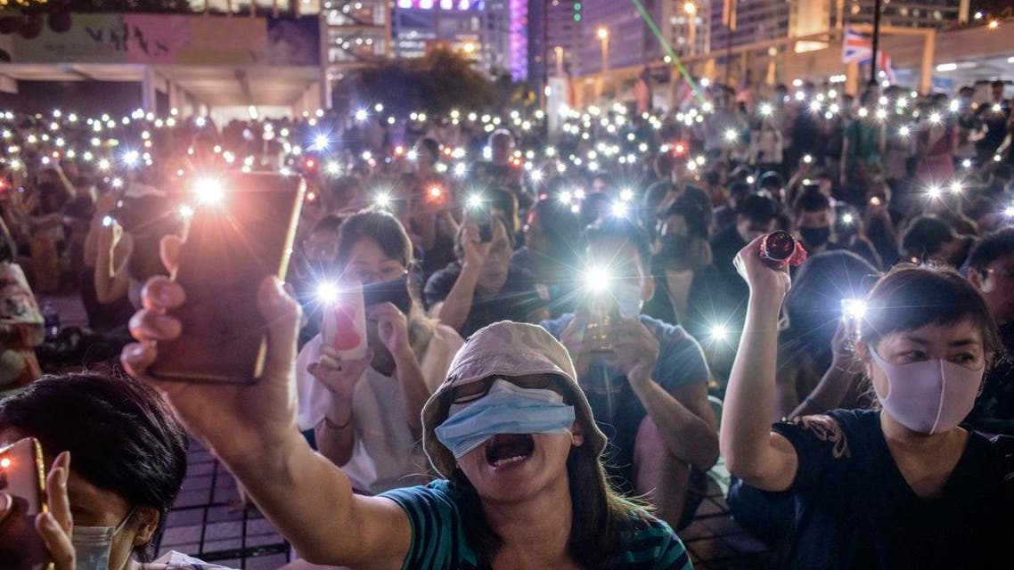 Attendees shout slogans and hold their mobile phones during a rally to show support for pro-democracy protesters in Hong Kong on October 19, 2019. (AP)