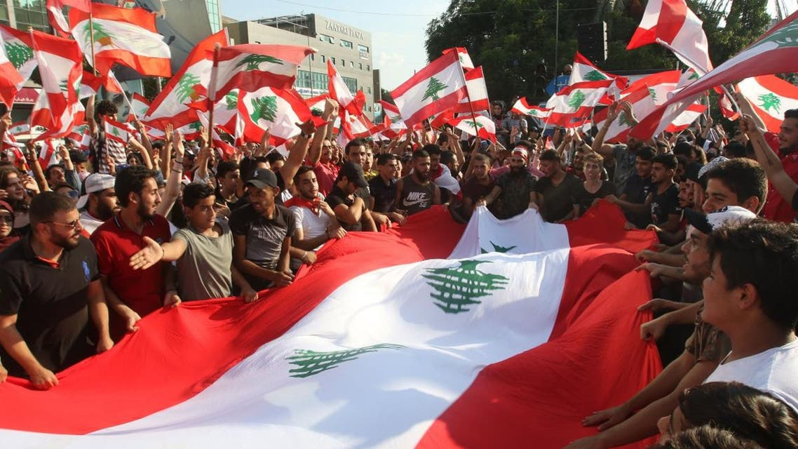 Lebanese demonstrators wave national flags as they take part in a protest against dire economic conditions in Lebanon's southern city of Sidon on October 20, 2019. (AFP)