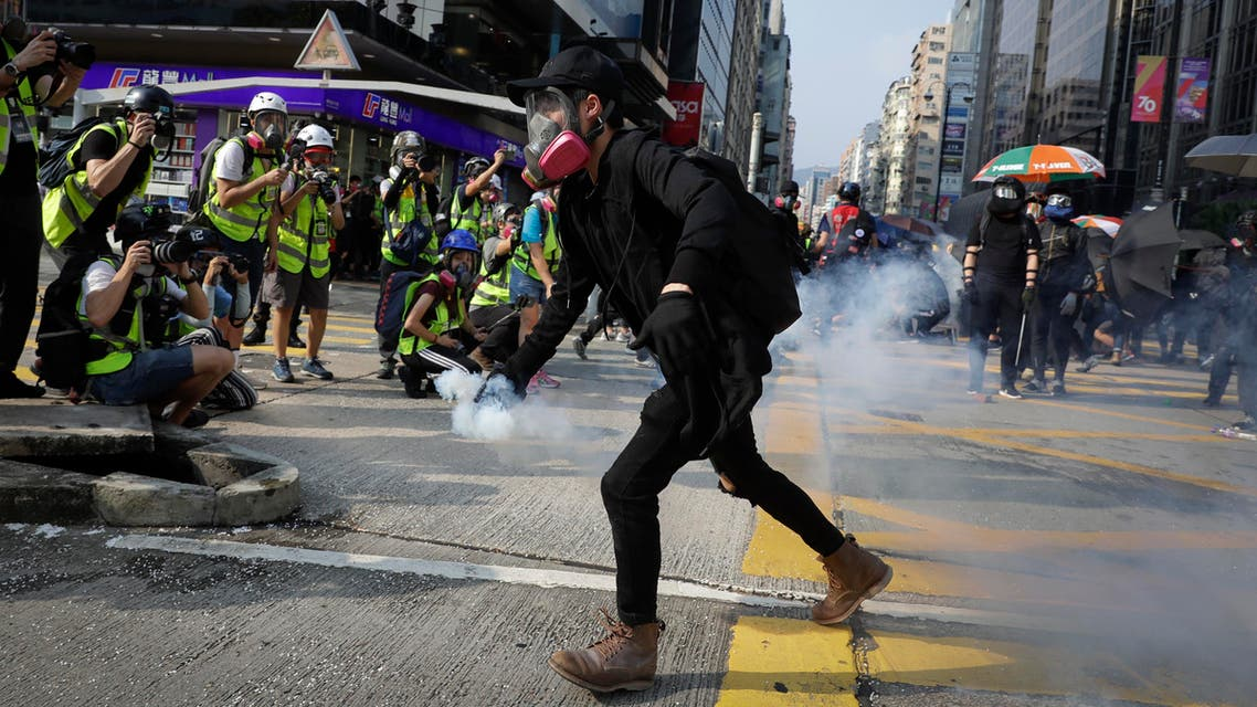 A protester carries away a tear gas canister during a rally in Hong Kong, Sunday, Oct. 20, 2019. (AP)