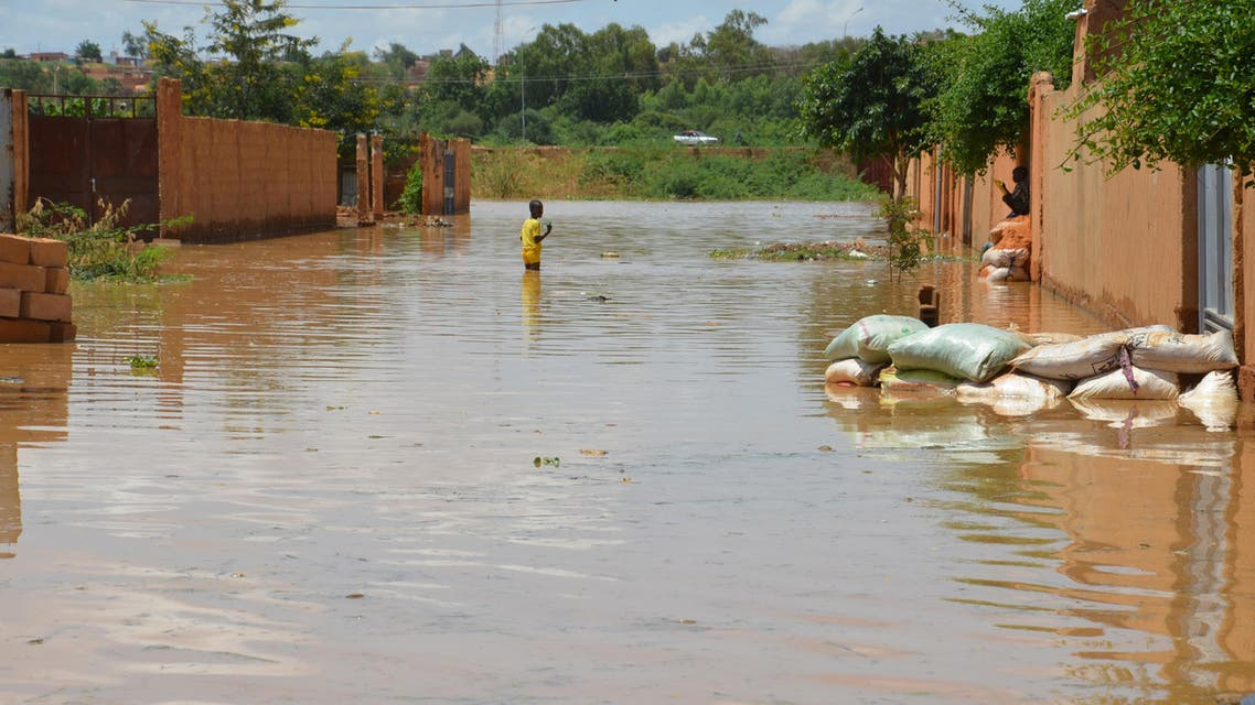 A child wades through water on a flooded street in the Kirkissoye quarter in Niamey on September 3, 2019. (AFP)