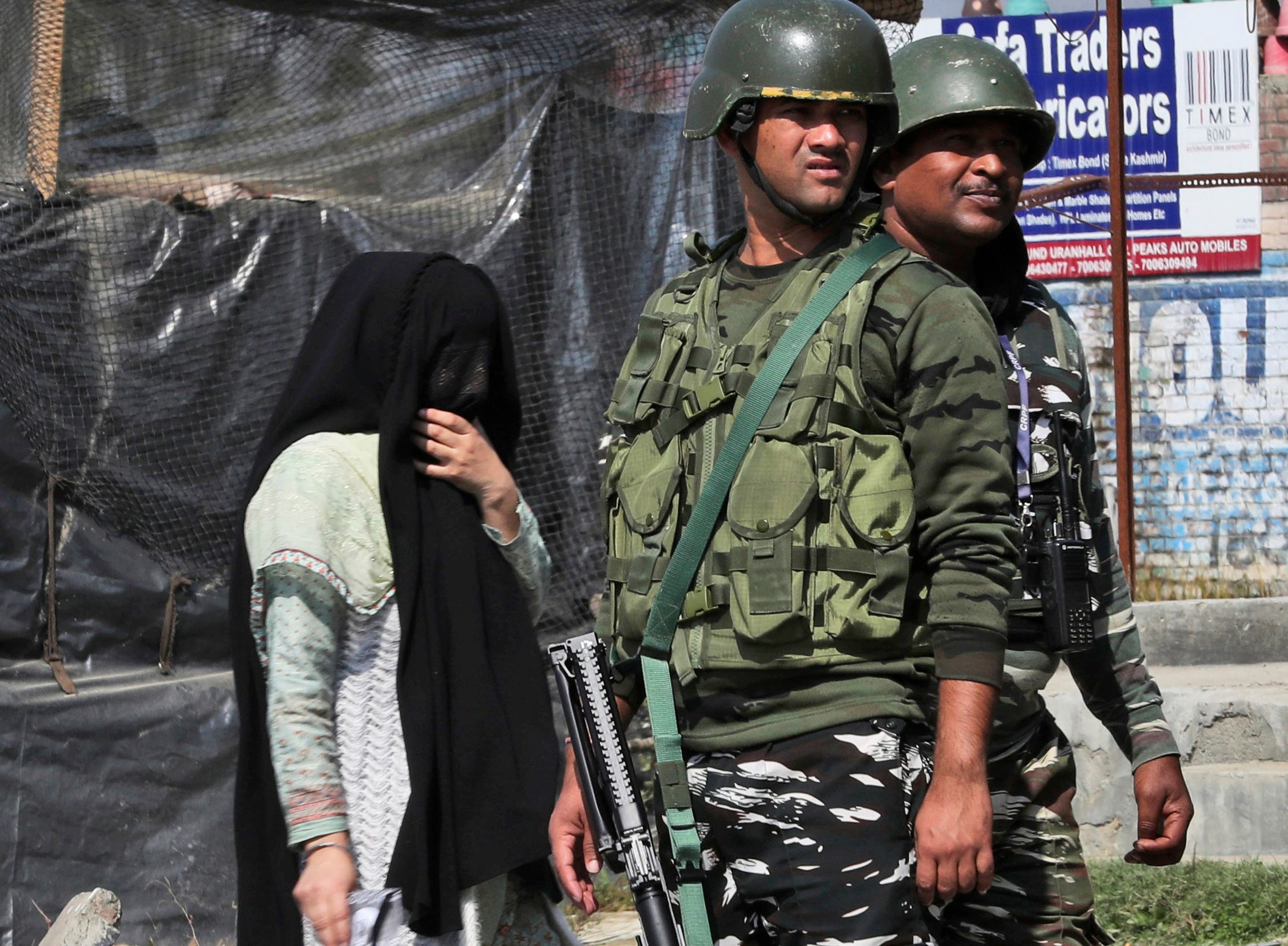 A Kashmiri woman walks past paramilitary soldiers standing guard near the site of a gunbattle in Bijbehara, south of Srinagar, Indian controlled Kashmir, Wednesday, Oct. 16, 2019. (AP)