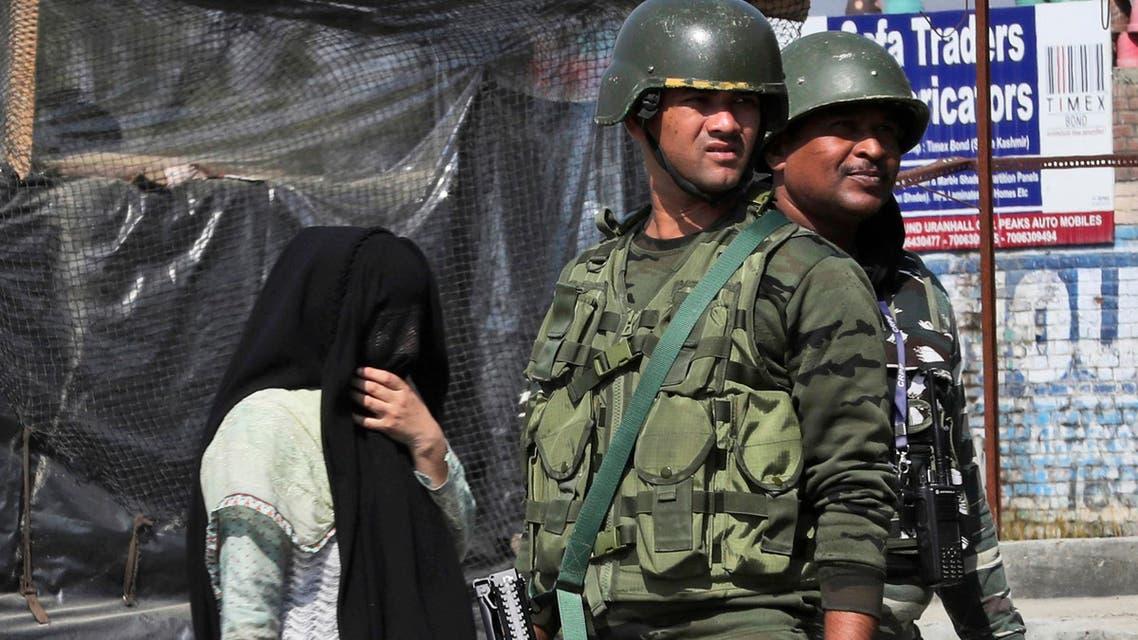A Kashmiri woman walks past paramilitary soldiers standing guard near the site of a gunbattle in Bijbehara, south of Srinagar, Indian controlled Kashmir, Wednesday, Oct. 16, 2019. (AP)