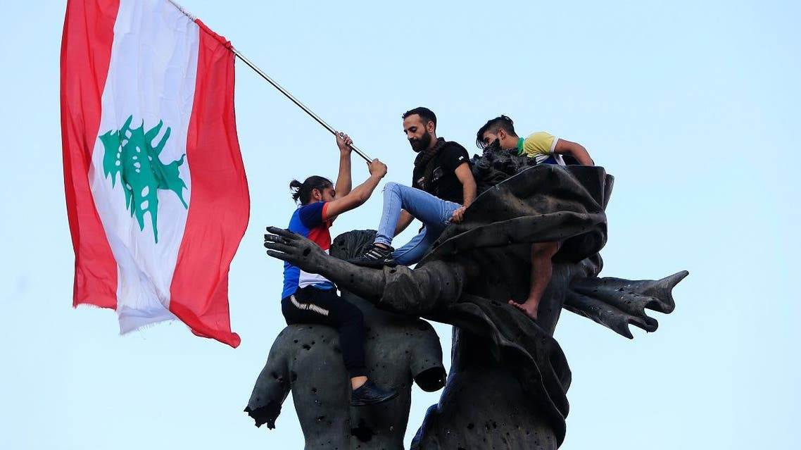 Demonstrators stand on a statue in Martyrs' Square during an anti-government protest in downtown Beirut. (Reuters)