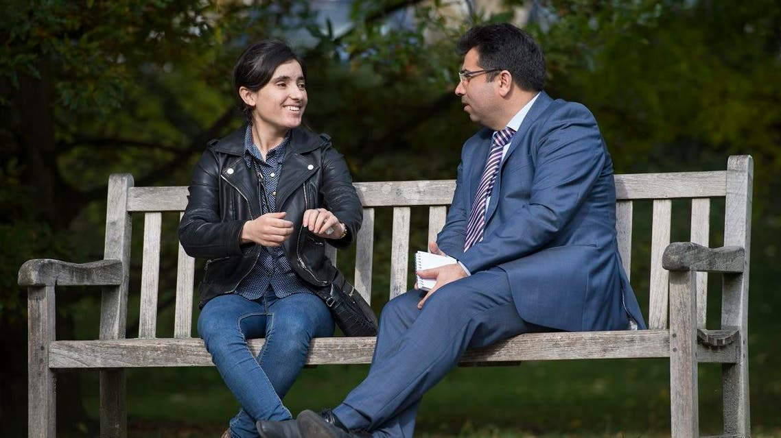 "Lamia Haji Bashar (L) and Mirza Dinnayi, chairman of the ""Luftbrücke Irak"" (airlift Iraq), talk in a park in Stuttgart, southwestern Germany. (AFP)"