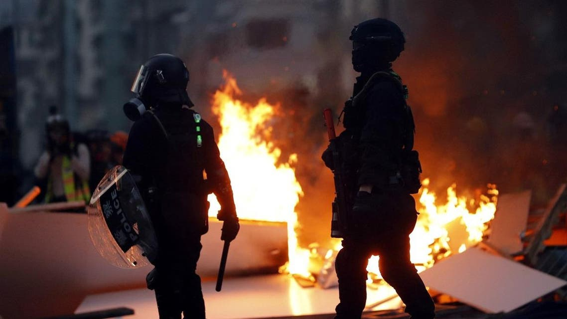 Police officers stand next to a burning barricade during an anti-government protest in Hong Kong. (Reuters)
