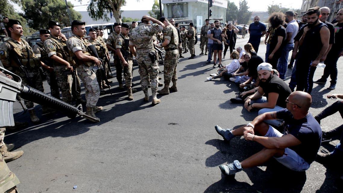 متظاهرون يفترشون الأرض أمام عناصر من الجيش اللبناني في إحدى ضواحي بيروت