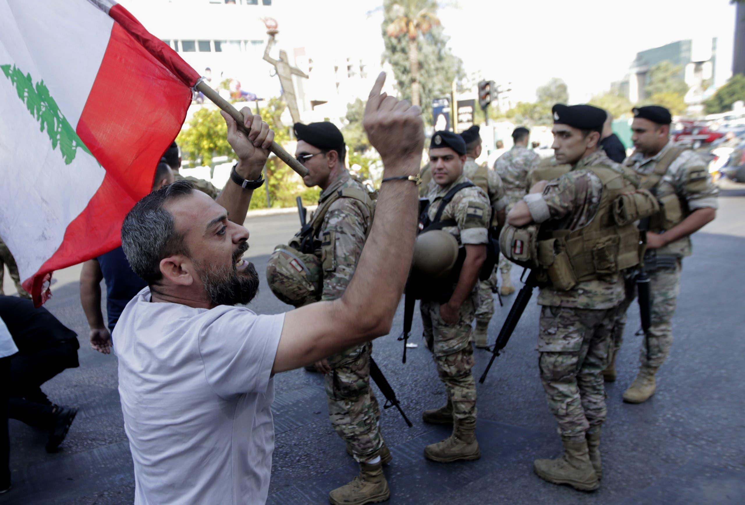 أحد المتظاهرين ووراءه عنصار الجيش في إحدى ضواحي بيروت