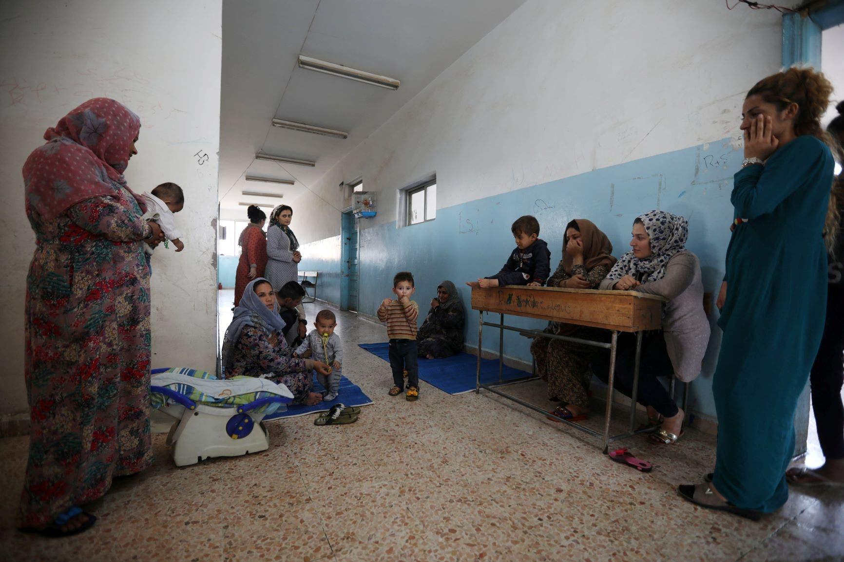 نساء نازحة واطفالهن بانتظار مساعدات في مدرسة شمال سوريا