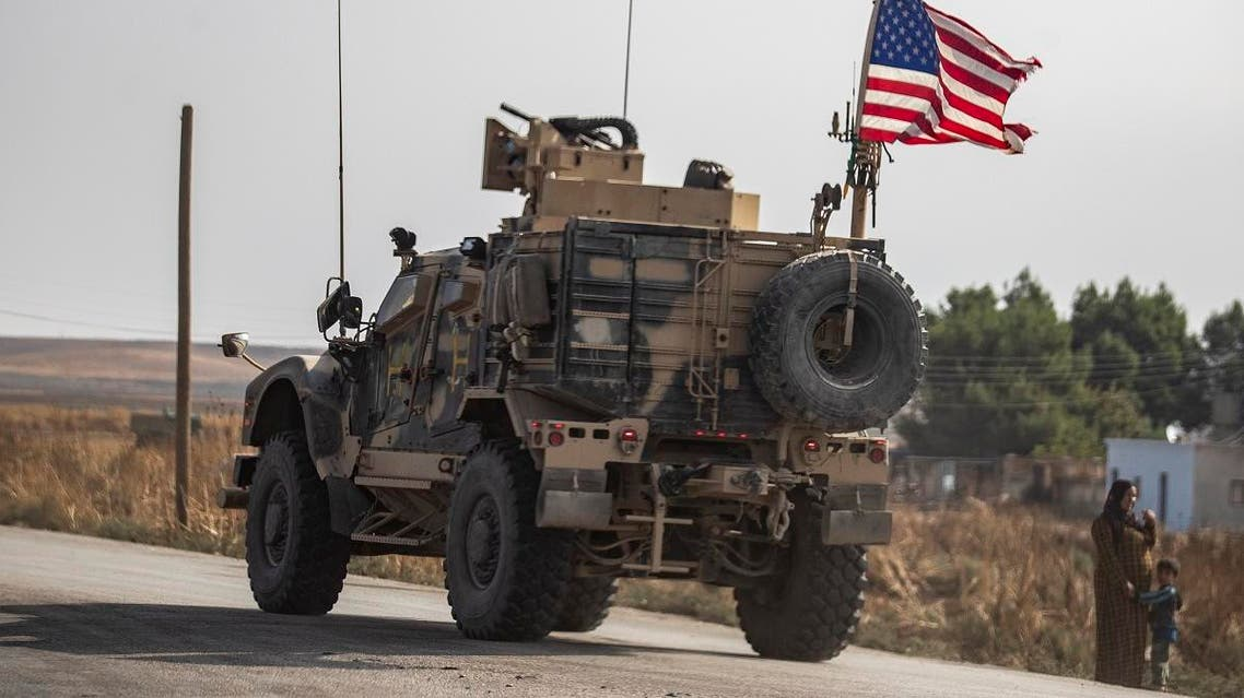 A Syrian woman and a child stand on the side of a road as a US military vehicle drives on a road after US forces pulled out of their base in the Northern Syriain town of Tal Tamr, on October 20, 2019. (AFP)
