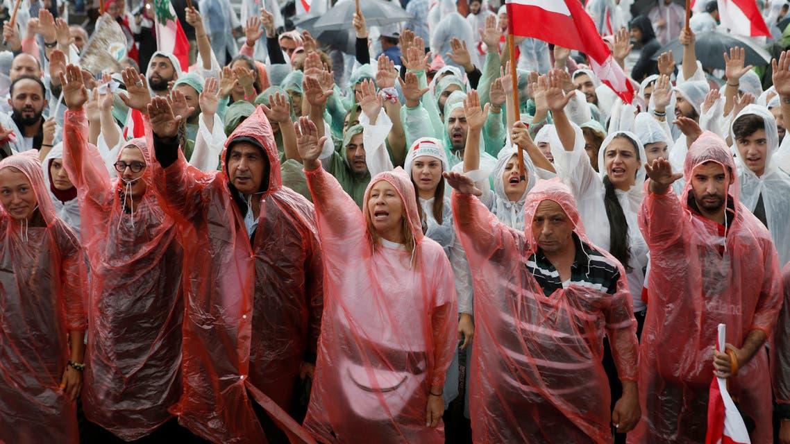محتجون لبنانيون يلوحون بالأعلام مرتدين معاطف المطر في بيروت الخميس
