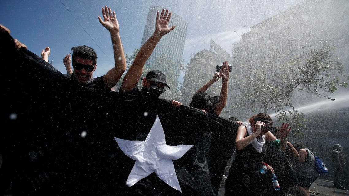 Anti-government demonstrators brace against the force of a police water canon during a general strike in Santiago, Chile. AP