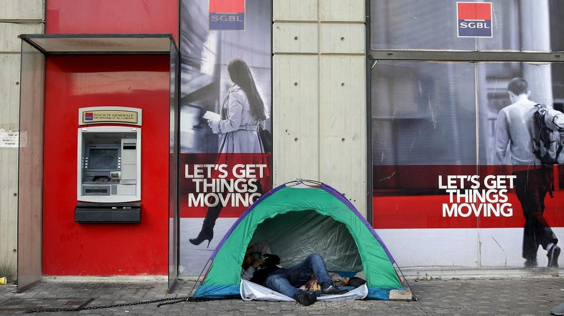 A Lebanese protester rests in a tent set up at the entrance of a bank in downtown Beirut. (AFP)