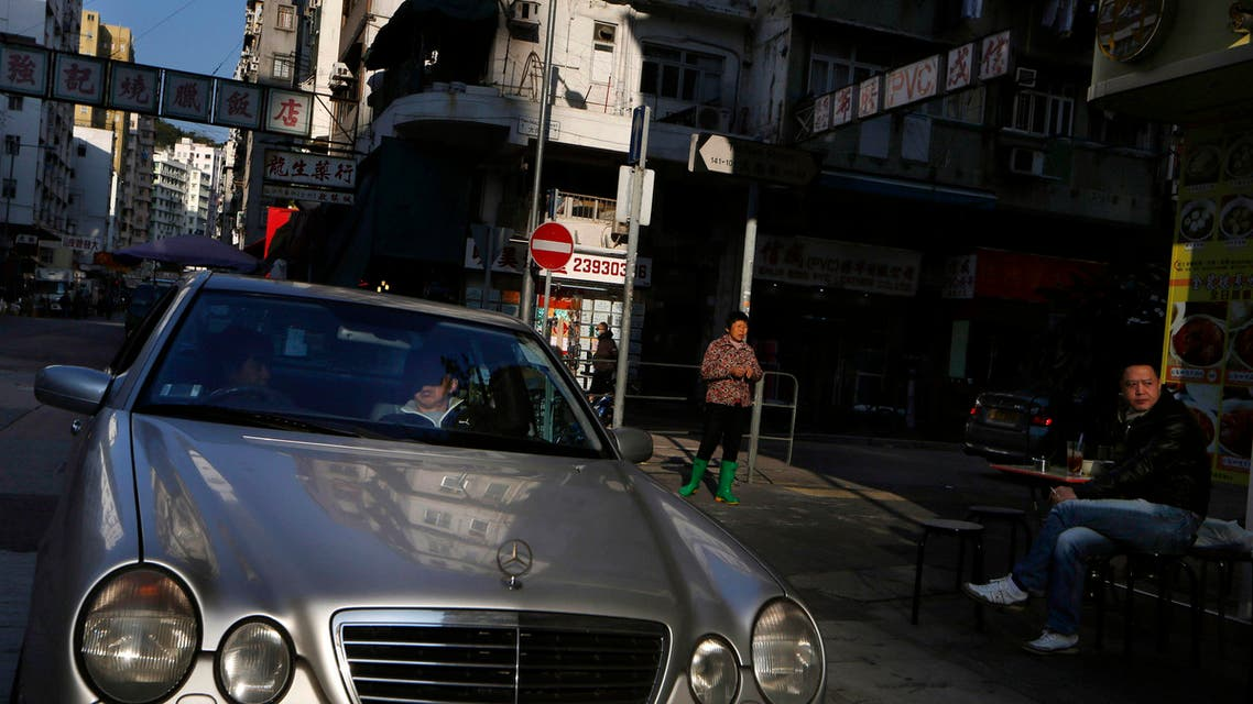 A luxury car parks at an old district area in Hong Kong (AP)