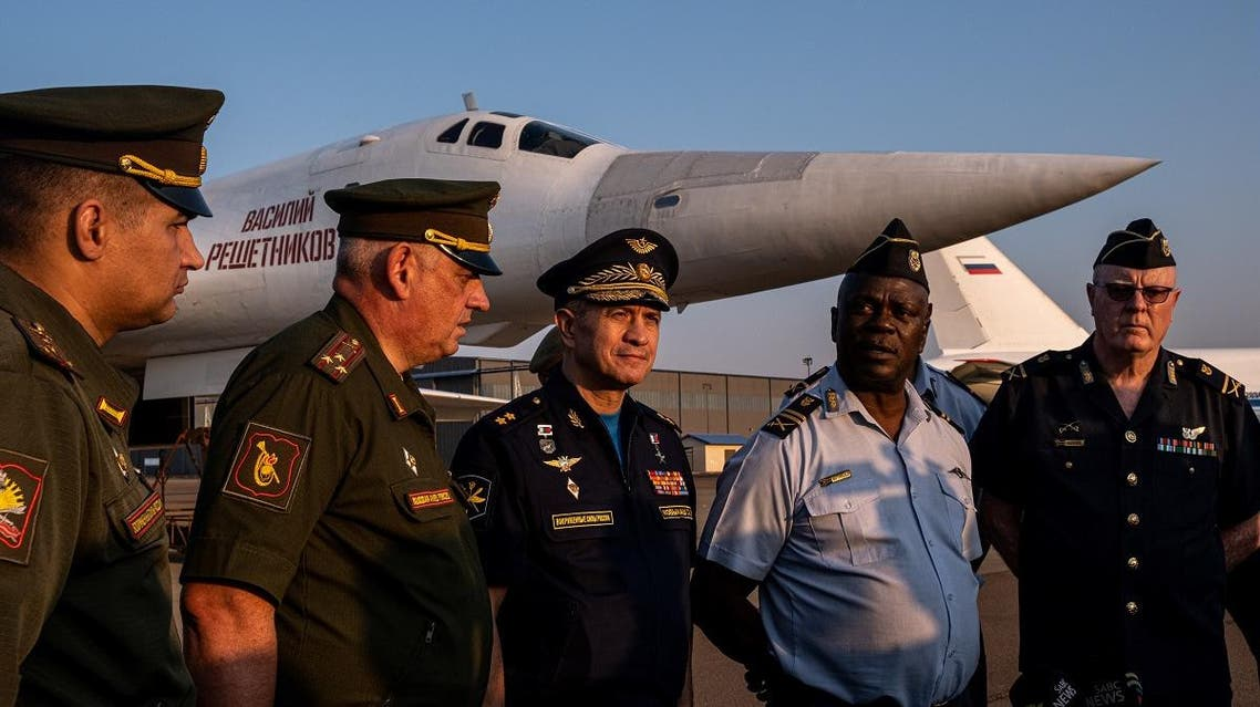 """Russian and South African officers speak in front of a Russian Air Force Tupolev Tu-160 """"Blackjack"""", a supersonic variable-sweep wing heavy strategic bomber, is parked on the tarmac at the Waterkloof Air force Base in Centurion, south of Pretoria, northeastern South Africa, on October 23, 2019. (AFP)"""