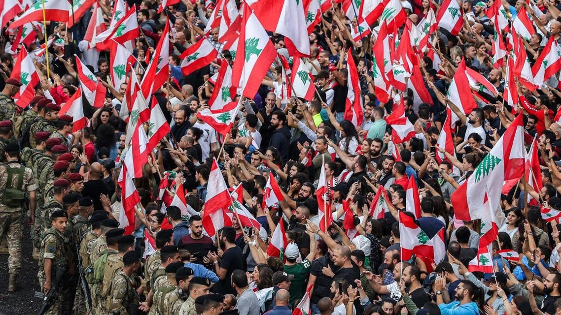 Protesters stand with Lebanese national flags before Lebanese army soldiers along the side of the Beirut-Jounieh highway in the northern Beirut suburb of Jal el-Dib amidst on the seventh day of protest against tax increases and official corruption, on October 23, 2019. (AFP)