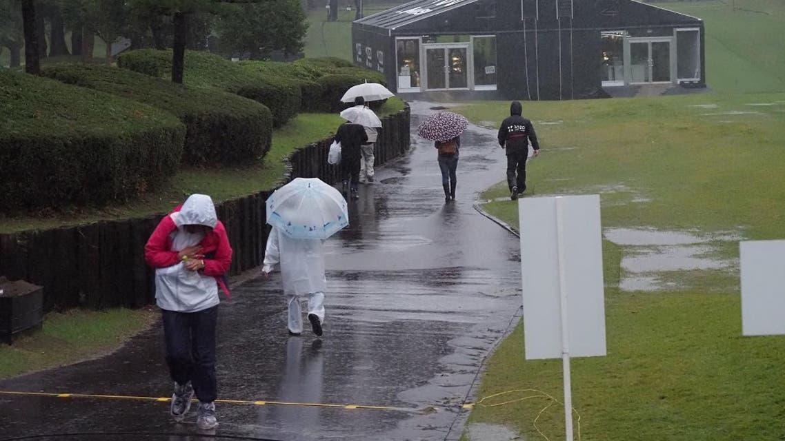 Spectators walk in the rain as the PGA ZOZO Championship golf tournament had been postphoned at the Narashino Country Club in Inzai, Chiba. (AFP)