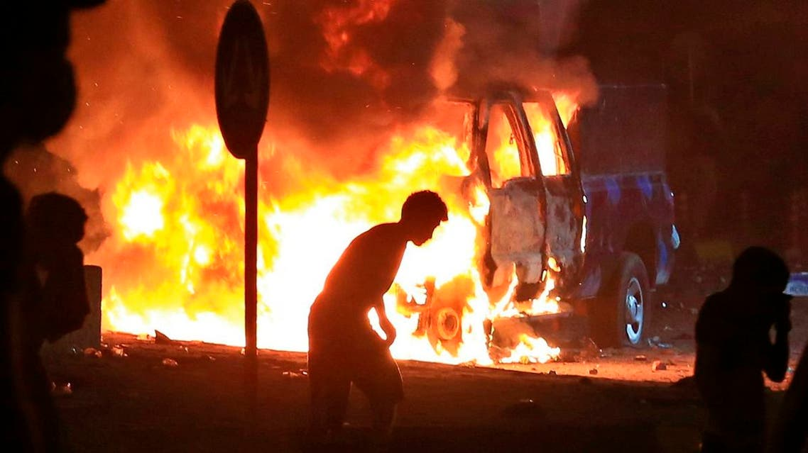 Anti-government protesters burn police vehicles guarding the provincial council during a demonstration in Basra, Iraq. (AP)