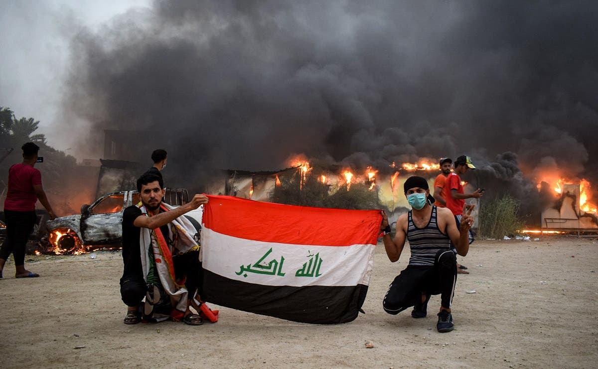 Iraqi protesters pose with a national flag during an anti-government demonstration outside the burning local government headquarters in Nasiriyah. (AFP)
