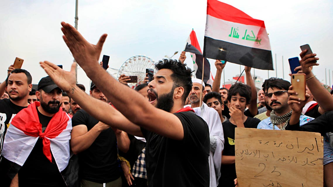 """Anti-government protesters chant slogans and hold a placard with Arabic that reads """"Iran out, all Islamic parties I want my right"""" during a demonstration in Basra, Iraq, (AP)"""