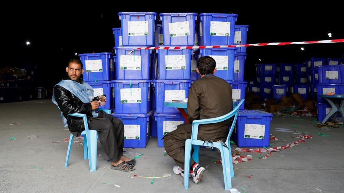 Afghan election commission workers sit next to ballot boxes and election material at a warehouse in Kabul. (Reuters)
