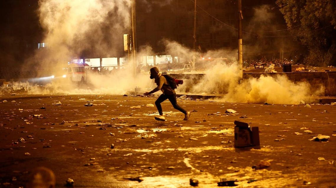 A demonstrator runs away from tear gas fired by Iraqi security forces during a protest in Baghdad. (Reuters)