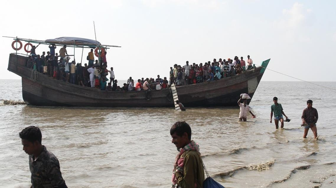 People get off a boat in Bhashan Char island off the Bangladeshi coast, as it was being prepared for the relocation of Rohingya refugees living in the country's south. (AFP)