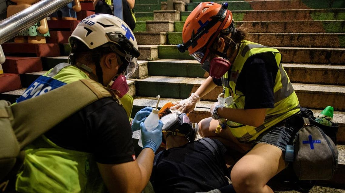 This picture taken on August 3, 2019 shows a man (C) lying on his back as he receives treatment from volunteer medics after he was affected by tear gas during a protest in the Tsim Sha Tsui area of Hong Kong's Kowloon district. (AFP)