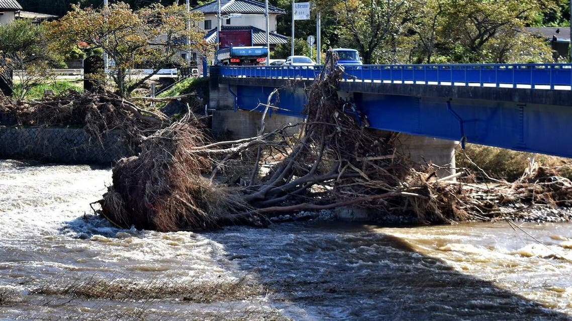 Damaged trees move along a flooded river after heavy rain in Iwaki city, Fukushima prefecture on October 26, 2019. Rescuers worked by hand to clear debris from a landslide triggered by heavy rains in central Japan on October 26. (AFP)