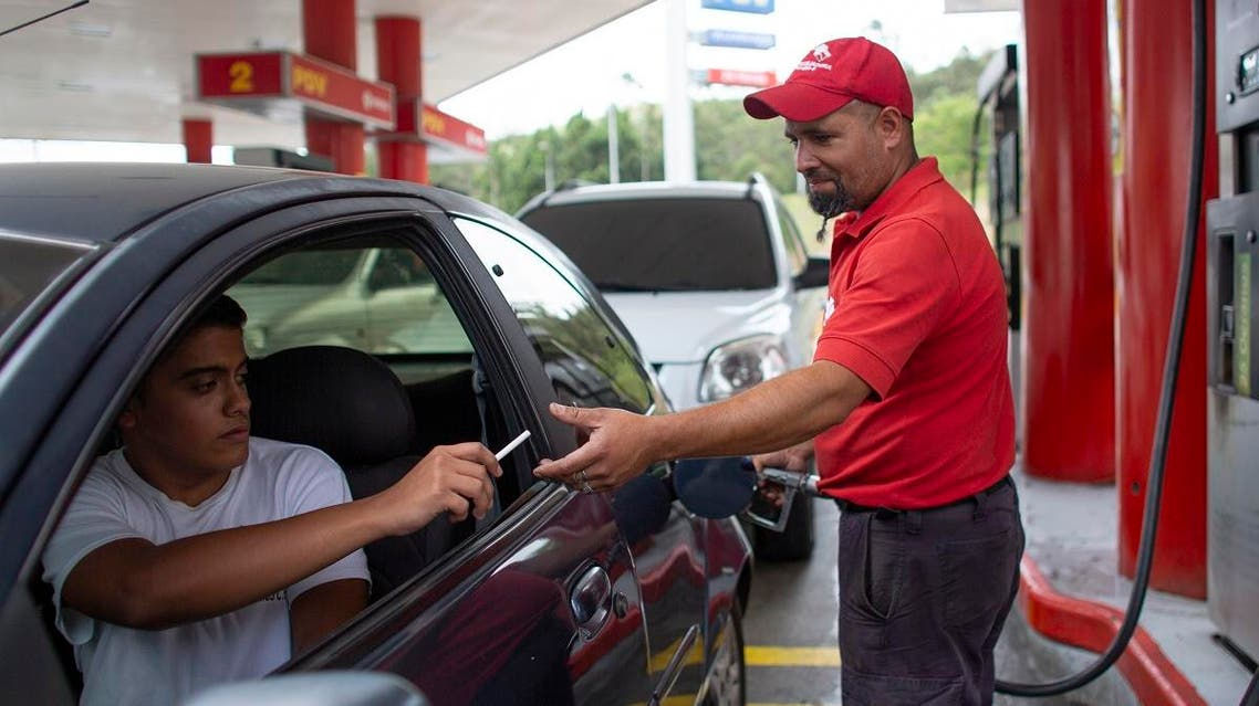 gas station attendant Leowaldo Sanchez takes a cigarette as payment from a motorist as he fills the tank in San Antonio de los Altos. (AP)
