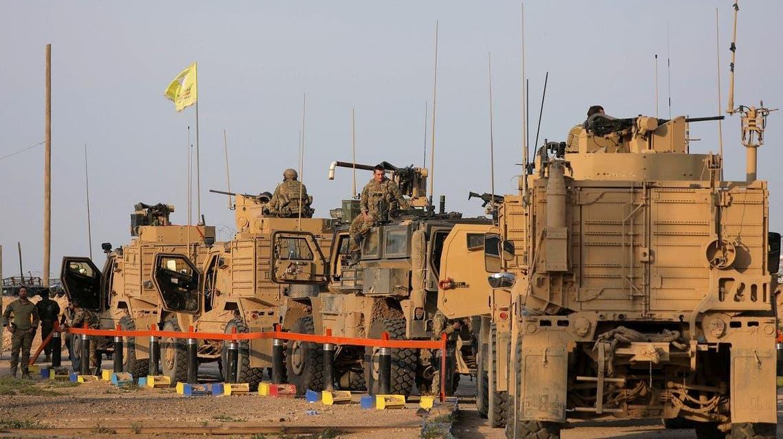 American soldiers stand near military trucks, at al-Omar oil field in Deir Al Zor on March 23, 2019. (Reuters)