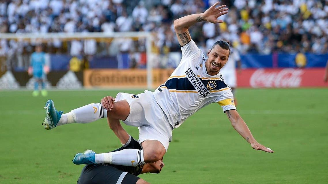 LA Galaxy forward Zlatan Ibrahimovic, top, falls to the ground as he is tripped by Vancouver Whitecaps FC defender Jasser Khmiri while battling for the ball during the first half of an MLS soccer match in Carson, Calif., Sunday, Sept. 29, 2019. (AP)