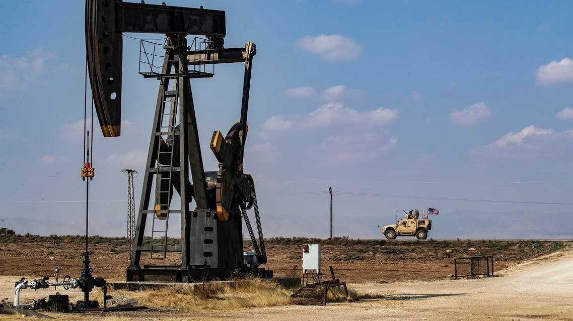 A US military vehicle, part of a convoy arriving from northern Iraq, drives past an oil pump jack in the countryside of Syria's northeastern city of Qamishli on October 26, 2019. (AFP)