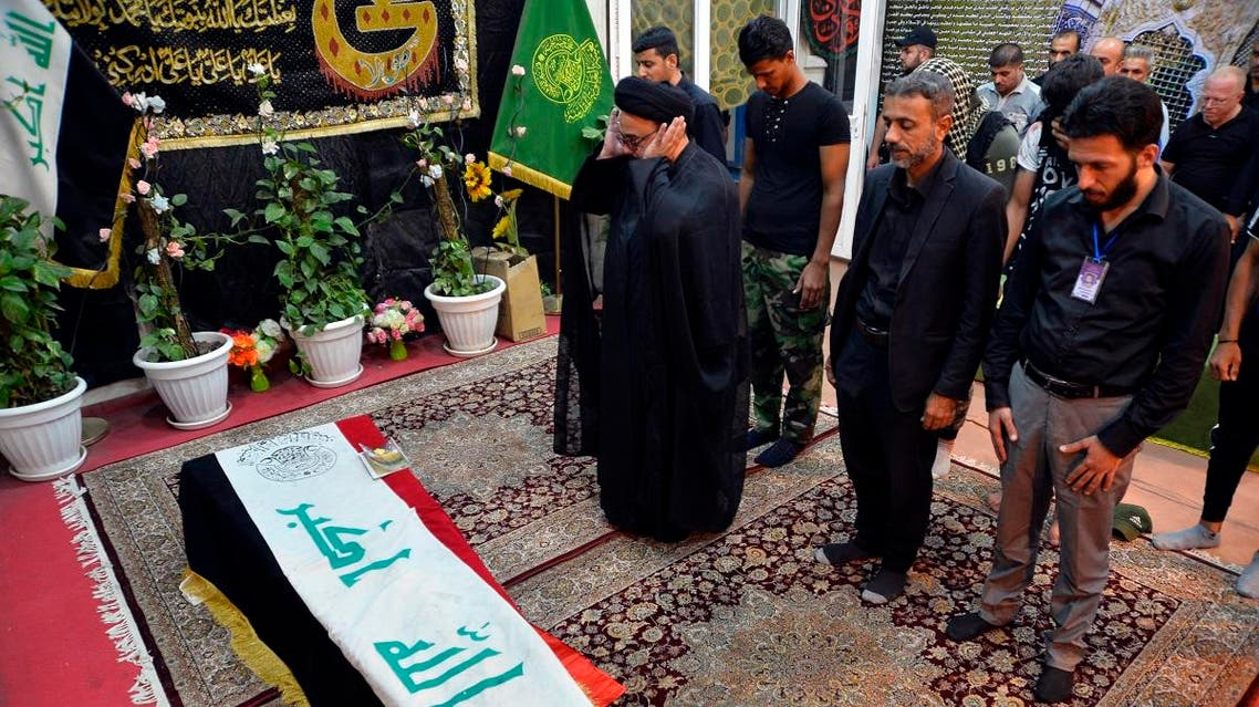 Mourners pray over the flag-draped coffin of a member of Iraq's Shiite Muslim Hashed al-Shaabi (Popular Mobilization units) paramilitary force during his funeral in the central holy shrine city of Najaf on October 26, 2019. (AFP)
