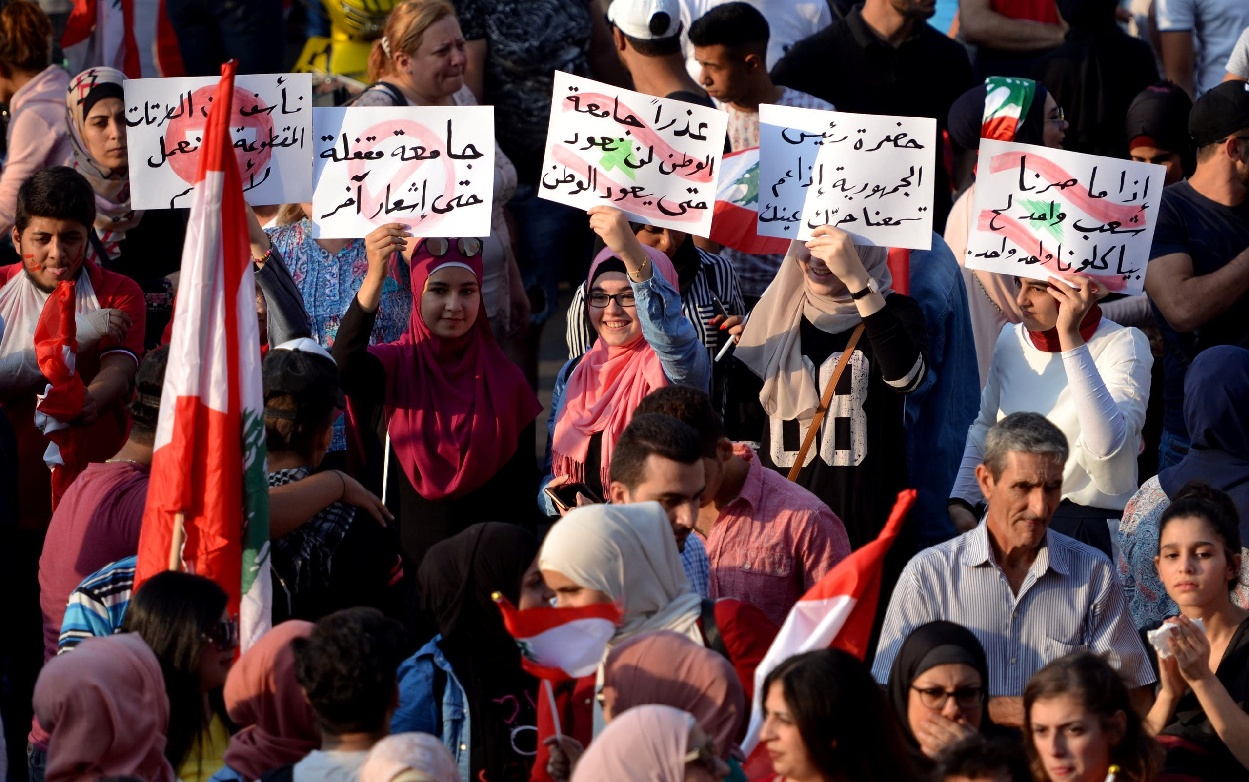 Protesters carry signs in Tripoli, Lebanon (Reuters)