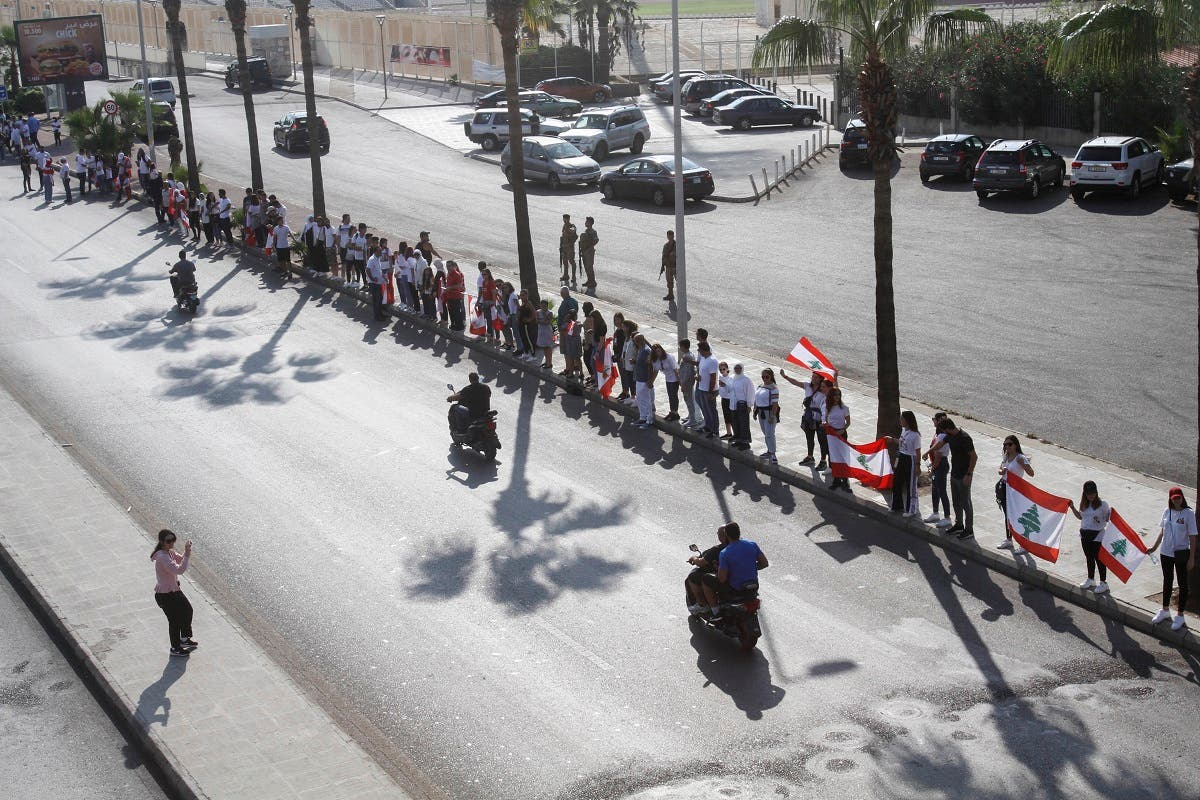 Lebanese protesters hold hands to form a human chain along the coast from north to south as a symbol of unity, during ongoing anti-government demonstrations in the southern Lebanese port city of Sidon on October 27, 2019. (AFP)