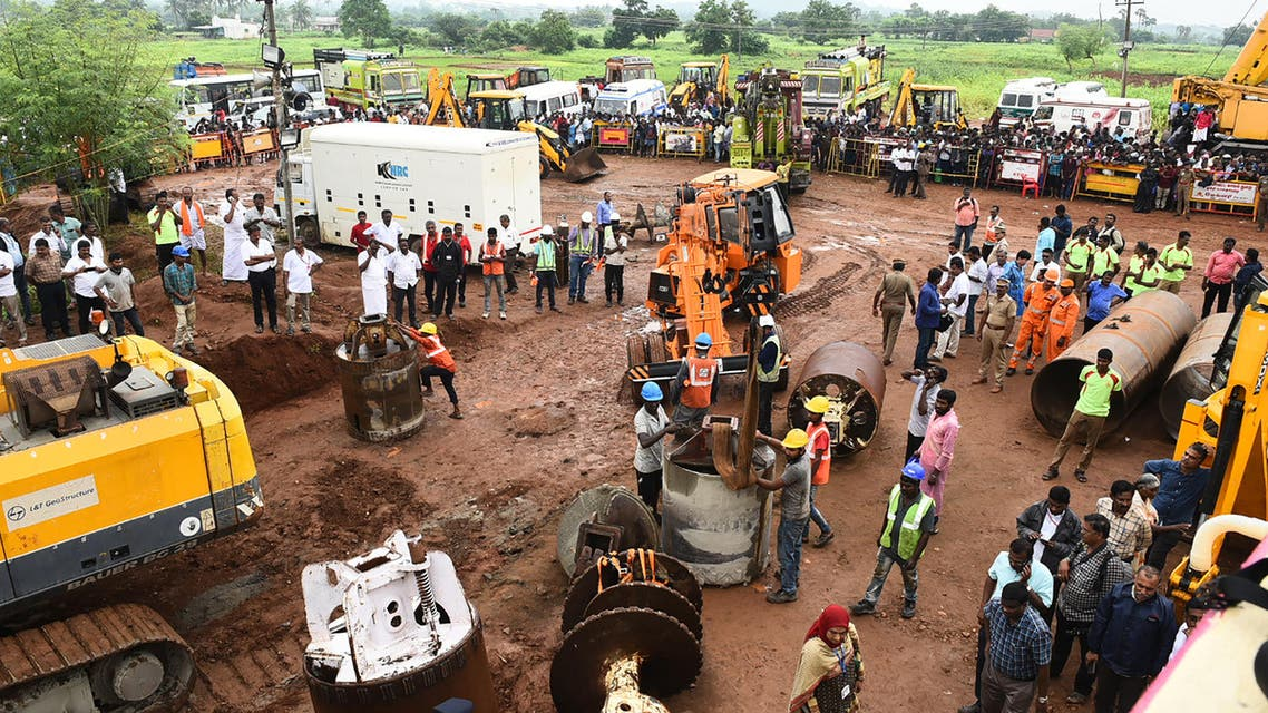 Rescue workers gather with heavy digging equipment during an operation to rescue a toddler stuck in a deep well near Manapparai town in Tiruchirappalli district (AFP)