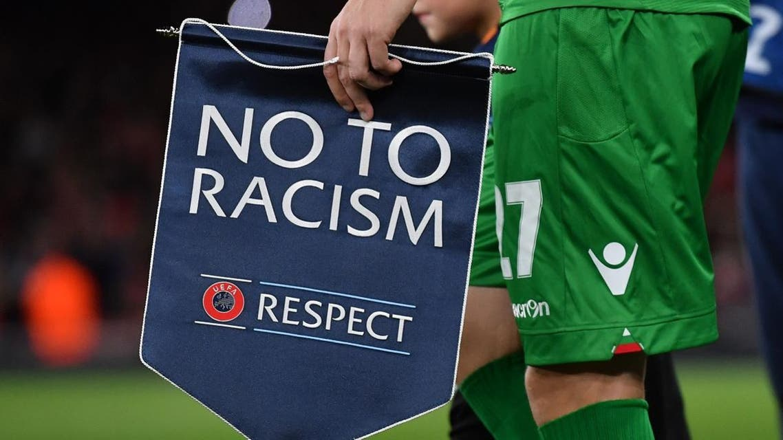 Ludogorets' Romanian defender Cosmin Moti holds an anti-racism banner ahead of the UEFA Champions League Group A football match between Arsenal and Ludogorets Razgrad at The Emirates Stadium in London on October 19, 2016. (AFP)