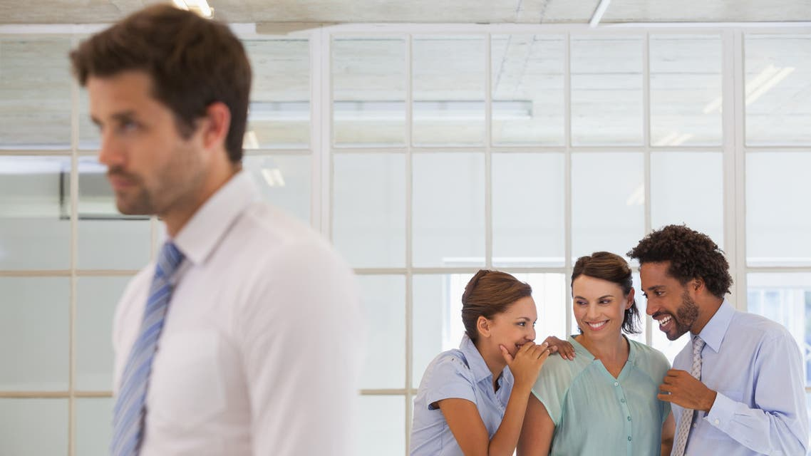 Colleagues gossiping behind a sad businessman stock photo