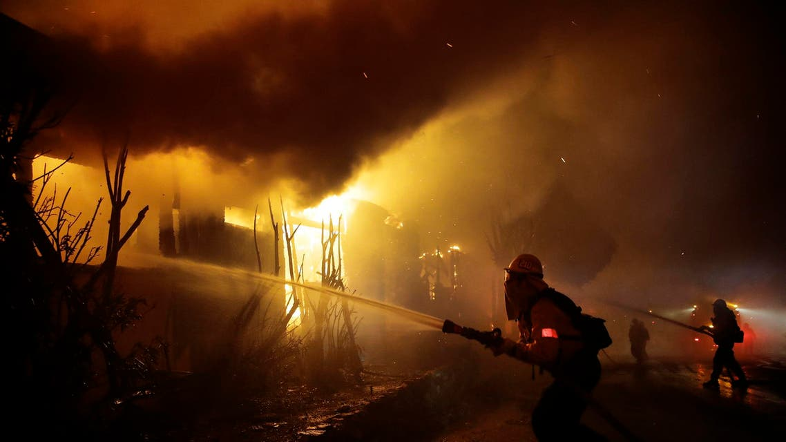 Firefighters try to hose down flames as homes burn in the Getty fire area along Tigertail Road, Monday, Oct. 28, 2019, in Los Angeles. (AP)