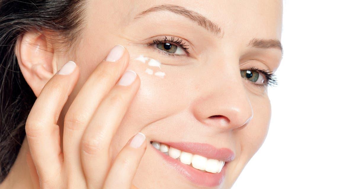 Skin care woman putting face cream stock photo