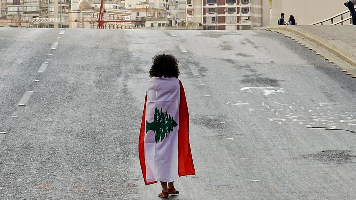 A Lebanese woman protester walks draped in a national flag along the Fuad Chehab avenue, near the Martyrs' Square, in the centre of the capital Beirut. (AFP)