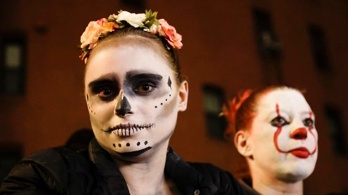 Leni Wild poses with others as they watch revelers march during the Greenwich Village Halloween Parade. (AP)