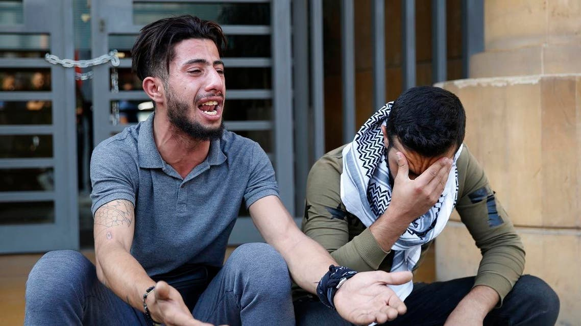 Anti-government protesters cry after riot policemen beat and arrest their friends who entered the building of the Lebanese Association of Banks and locked the main entrance by a chain and lock, during ongoing protests against the banks policies and Lebanese government, in Beirut, Lebanon, Friday, Nov. 1, 2019. (AP)