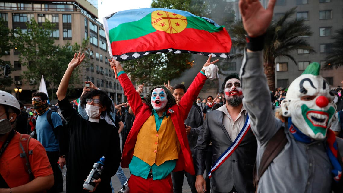 A man dressed as the Joker and holding a Mapuche flag cheers with others dressed in costumes during an anti-government protest in Santiago, Chile, Friday, Nov. 1, 2019. (AP)