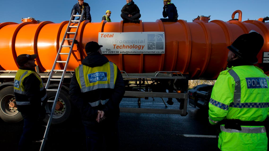 Police prepare to remove a protestor from the top of a vehicle waiting to enter an exploratory drill site for the controversial gas extraction process known as fracking at Barton Moss in Manchester, England, Monday, Jan. 13, 2014. (AP)