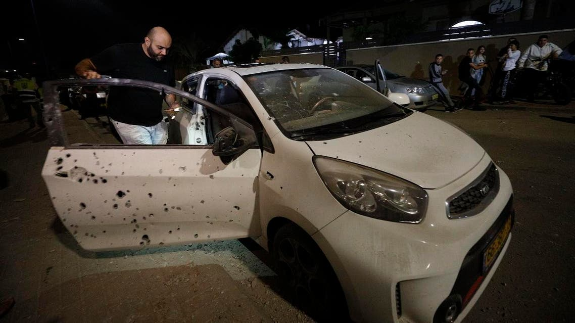 A man checks a car damaged iby shrapnel from a missile fired from Gaza Strip in Sderot, Israel. (AP)