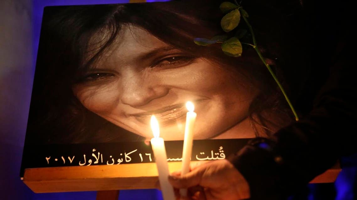 A Lebanese woman holds candles in front a portrait of the killed British citizen Rebecca Dykes, whose body was found on the side of a motorway in 2017. (AP)