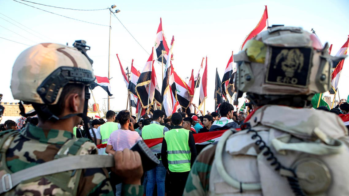 Iraqi security forces stand guard while anti-government protesters gather near Basra provincial council building during ongoing protests in Basra, Iraq, Friday, Nov. 1, 2019. (AP Photo)