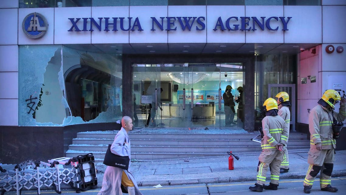 Firefighters stand outside the offices of China's Xinhua News Agency after its windows were damaged by protesters in Hong Kong, Saturday, Nov. 2, 2019. (AP)
