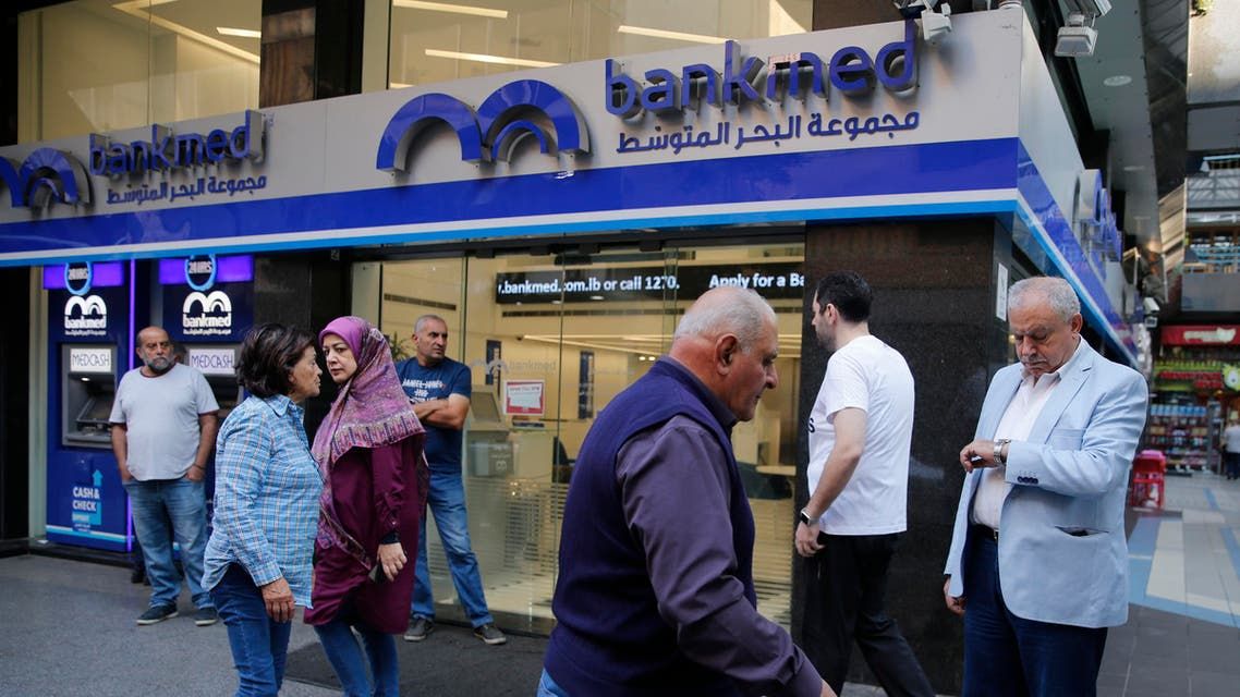 Lebanese clients wait outside a private bank for the opening after two weeks of closer, in Beirut, Lebanon, Friday, Nov. 1, 2019. Lebanon's private banks have reopened after a two-week closure because of anti-government protests. (AP)